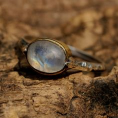 Moonstone cabochon ring in polished brass bezel setting with hand textured and oxidized silver band