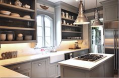 sink w/ open shelving w/ stovetop in island directly behind