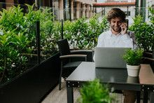 Smiling businessman in outdoor cafe working on laptop and talking on phone
