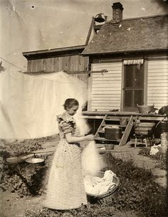 Woman hanging laundry on clothesline. Decorah, Iowa. ca1903-1905. Marsh Collection. State Historical Society of Iowa.
