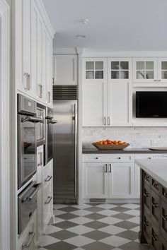 Amazing kitchen design with white & gray checkered floor, creamy white shaker kitchen cabinets with gray quartz countertops, marble subway tiles backsplash, walnut kitchen island with white quartz countertop, TV and warming drawer.