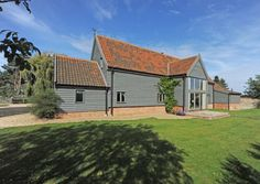 This striking barn conversion is on the edge of Tunstall, about four miles from Orford on the coast, and miles from the market town of Woodbridge. Barn Conversion Exterior, Bungalow Conversion, Barn Conversions, England Houses, New England Homes, House With Porch, House Front, Garage Extension, External Cladding