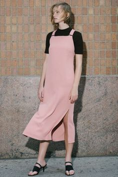 Nude pink pinafore dress of a black high neck t-shirt and black sandals with button heel. Nomia, Resort 2017