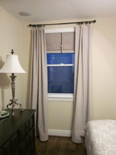 DIY drapes for my bedroom made from painters drop cloth along with a roll down shade for room darkening.  I used a flat sheet I purchased from Wal-Mart for $4.75 to line each drapery panel.  The total cost of the project was less than $40.00 per window.