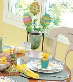 For a departure from a traditional arrangement, gather bright-hued egg-themed stakes in a glass candleholder filled with flat marbles and ivy.