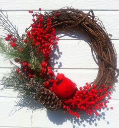 This versatile grapevine wreath can easily be used for Christmas as well a door display throughout the Winter months. A plump vibrant red bird sits amongst bright red berries, branches with crystal ice droplets, artificial pine and a pine cone. This little birdie would like nothing more than to be part of your holiday décor.    Measures 18 in length and 21 wide    Keep in a protected area.