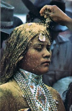 The Apache Sunrise Ceremony celebrates a girl becoming a woman. Girls prepare for the ritual for six months or more. During the ceremony, which can last four days, the girls sing, pray, run, and dance, often for hours without stopping. Here, a girl from the White Mountain Apache tribe in Arizona is blessed with pollen, symbolizing fertility.