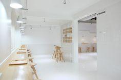 Thaipan Studio utiliza 12.000 azulejos blancos y madera clara en el nuevo establecimiento de la cadena Butterfly Organic Milk, en Bangkok (Tailandia)