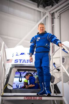 Astronaut Eric Boe, clad in Boeing's blue spacesuit, poses for a photo at the hatchway of the company's CST-100 Starliner module.