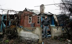 A man stands in front his damaged house after shelling in the Ukrainian town of Makeevka (CNS)
