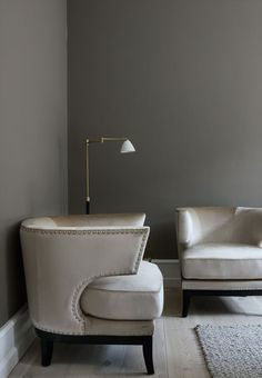 Elegant corner in the living room featuring a golden floor lamp and armchairs in sand colored velvet.