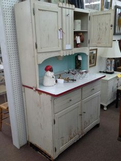$345 - This antique Hoosier style kitchen cabinet has the original flower bin and white chippy paint, porcelain pull out counter top, white with a red band. Lots of storage...a great vintage look. It measures 40x23x69 inches.  It can be seen in booth B 12 at Main Street Antique Mall 7260 East Main St ( E of Power Rd ) Mesa 85207 480 9241122 open 7 days 10 till 530 Cash or charge 30 day layaway also available