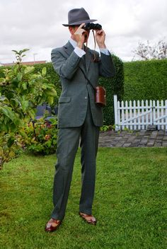 """Thornproof tweed in grey/green hues, white shirt (double cuff, detachable double round collar), Cheaney """"Edwin"""" co-respondent shoes and a vintage set of binoculars"""