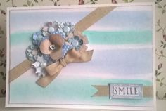 I inked the background with Cosmic Shimmer Colour Cloud inks in Frosty Aqua and Frosty Blue. I created the scruffy stripes by dragging the Creative Expression Smoothies across the page. The paper flowers are from Craftwork Cards Serenity collection.