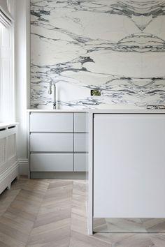 Minimalist kitchen with marble splashback and chevron oak floor