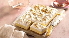 Starts At Sixty!   Lemon meringue cheesecake slice 250g digestive biscuits, finely crushed 125g butter, melted 1/4 cup lemon curd 500g cream cheese, softened 3/4 cup caster sugar 3 teaspoons gelatine dissolved in 1/4 cup boiling water, cooled 300ml thickened cream Finely grated zest and juice of 1 lemon Meringue (see below) Method