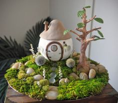 custom night light - house handmade from paper clay with an electric candle light placed inside.  surrounded by live or fake greenery / succulents.