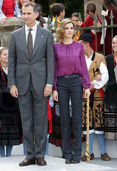 La Reina Letizia de España con conjunto de pantalón gris de talle alto y camisa morada abombada.