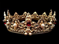 This is a full round golden crown designed to fit around the royal head. It has beautifully detailed fleur de lis points and brass filigree with