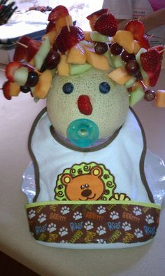 This is a fruit kabob display I created for a baby shower.  Use a cantalope, blueberries, strawberries, melon, grapes etc.  Decorate cantalope with a baby bib.  Carve a small hole and pop in a pacifer.  Warning, you will need to place the cantalope in a shallow bowl to hold it so it won't roll around as you add the fruit kabobs.