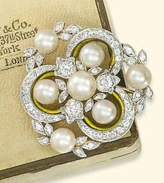 ANTIQUE VINTAGE 20TH CENTURY PEARL AND DIAMOND BROOCH, BY TIFFANY & CO. Of openwork design, the central pearl surrounded by circular-cut diamonds and three pearls of foliate motif to the diamond-set trefoil plaque with gold enamel detail, the outer surround composed of three pearls, each flanked by diamond-set leaves, mounted in platinum and gold, circa 1910, in case by Tiffany & Co. New York, signed Tiffany & Co. (Christies.com)