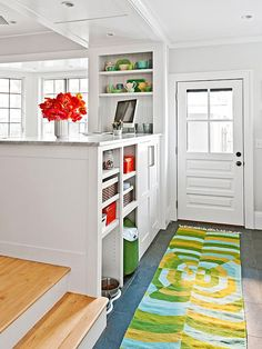 This back-door entry cleverly uses the backside of the kitchen cabinetry for storing items that transition between indoors and out—for example, pet gear, and shoes. Closed-door cabinets hide empty grocery bags, cleaning supplies, and other unsightly things