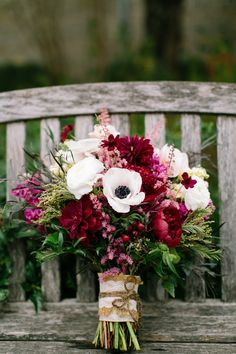 Wine colored peonies, anemones for pops of white, and greenery, a wildflower textured bouquet for fall wedding.