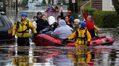 People, some waving to those on dry ground, are rescued by boat in Little Ferry, N.J. Tuesday, Oct. 30, 2012 in the wake of superstorm Sandy.