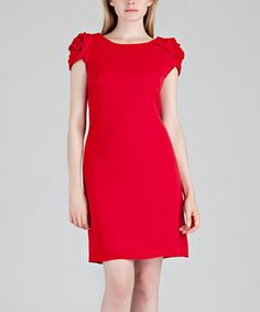 For an elegant evening, choose this flattering frock. Its rosette bedecked shoulders add decadent depth, while a boatneck silhouette complements the neckline.