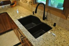 Double black Kitchen Sink with black curved faucet connected by white granite countertop.