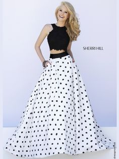 Show off a toned mid section in the Sherri Hill prom gown 32215! This prom gown features a beaded lace crop top with an adorable black and white polka dot skirt.   Features: Silhouette: A-Line   Neckline: Halter  Sizes Available: 00 - 14    Colors Available: Ivory/Black