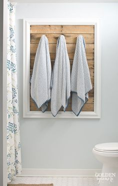 This unique towel rack for the bathroom combines plank wood, some hooks and a frame - from The Golden Sycamore | Friday Favorites at www.andersonandgrant.com