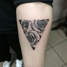 Simple and beautiful Triangle Glyph Tattoo. The design is in black and gray and you cans see that there are there roses within the triangle shape. This keeps the design in minimalist fashion.