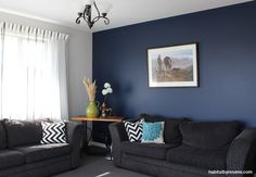 The artwork which inspired Selina and Earl's colour scheme (Taking a Breather by Julie Greig) hangs on a feature wall of Resene Midnight Express in the living room. Dark Blue Feature Wall, Blue Feature Wall Living Room, Living Room Colors, Cozy Living Rooms, Living Room Paint, Home And Living, Living Room Decor, Blue Lounge, Modern