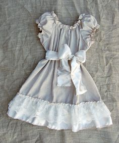 Lightweight and airy, this rustic beauty features an elastic neckline, billowing peasant sleeves and a dainty sash for a modern twist on a vintage-inspired look.Cotton / polyesterMachine washMade in the USA