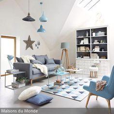 Blau-Grau dominiert dieses helle Wohnzimmer. Harmonierende Polstermöbel, Beistelltische, Teppich und Leuchten machen das Zimmer gemütlich und wohnlich. …