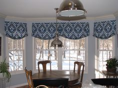 Relaxed roman shade valance in Ultra Marine Ikat pattern creates a stunning look in a kitchen bay. Designed by Terry Kral, Window Wear Etc.