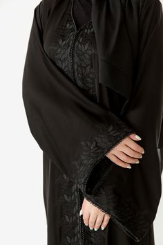 This effortless abaya with intricate leaf detailing and delicate beads on the front opening and sleeves, is a practical piece for both home and abroad. Matching scarf included.  Made in the UAE.