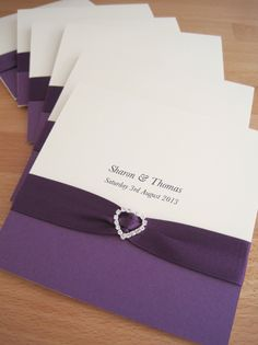 Albany Pocketfold Wedding Invitations in cream and purple and finished with purple ribbon and a crystal heart.