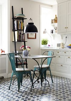 Here's a welcome mid-week daydream for you: a charming French bistro-inspired kitchen! This small kitchen has so much going for it — from the floor tiles (swoon!) to the teal metal chairs and the wrought-iron table legs...