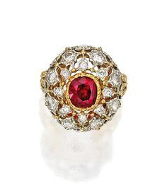 18 KARAT TWO-COLOR GOLD, RUBY AND DIAMOND RING, BUCCELLATI    Of openwork design, centered by a cushion-cut ruby weighing approximately 1.95 carats, framed by numerous round diamonds weighing approximately 1.45 carats, size 5¼, signed Buccellati Italy.