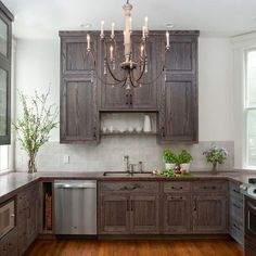 Cottage kitchen features a French candle chandelier illuminating dark stained cabinets paired with a dark stained wood countertop and a gray tiled backsplash laid out in a grid formation.