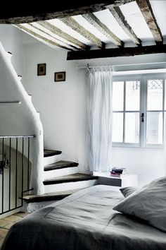 stairs leading down to a cozy bedroom