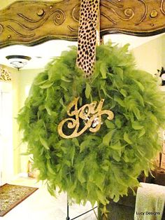 I wrapped a styro wreath form with a feather boa in that green color that I love, added an animal print ribbon to hang it and another word sign...Joy