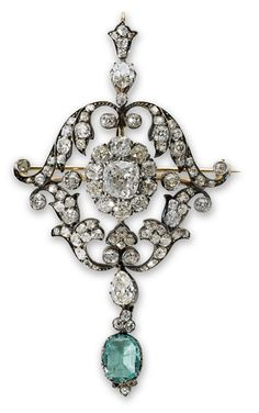 An antique emerald and diamond pendant brooch The cushion-shaped diamond within an old-cut diamond cluster set to the centre of a similarly cut diamond foliate frame and pendant bail, terminating in a pear-shaped diamond and oval mixed-cut emerald drop, mounted in silver and gold.