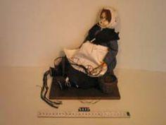 Pop (5632a) in klederdracht, voorstellende een vissersvrouw. Eénvoudige pop in klederdracht, witte wollen muts en replica sieraden. Zwarte rokken, geruit vest, wit schort, zwarte wollen omslagdoek, aan de linker mouw is een stukje visnet en een boetnaald vastgemaakt.  #ZuidHolland #Vlaardingen