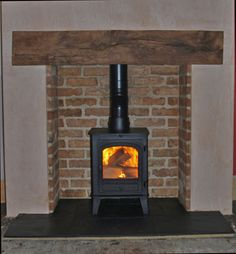 Reclaimed brick slip chamber with slate tiled hearth, clad oak beam and Parkray consort 4 wood stove. Fitted in Basildon Essex 2010