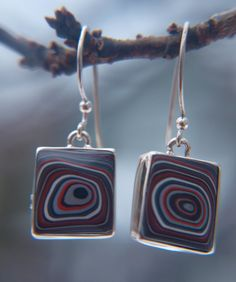sterling earrings with a piece of late 1960s Fordite. the fordite was cut and shaped in house (by my father or myself) the silverwork designed by us as well. this is one of my favorite things, recycled art.  what is fordite?  wikipedia states:  Fordite, also known as Detroit agate, is old automobile paint which has hardened sufficiently to be cut and polished.[1] It was formed from the build up of layers of enamel paint slag on tracks and skids on which cars were hand spray-painted (a now…