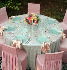 Credit: Wildflower Linens  Pink tutu inspired chair covers over chivari chairs.  Light blue sequin tablecloth.  Seaglass inspired stacked square plates, with a ballet slipper pink napkin. Wedding Reception Tables & Venue