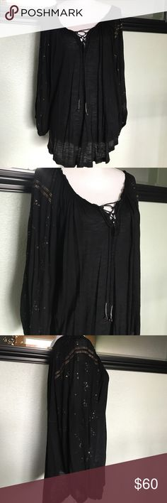 Free People boho top BEAUTIFUL black Free People top. Deep scooped neck with cross tie at chest. Ties are long and end in tinkly bells. Long sleeves with elastic cuffs. Very loose fit. Gorgeous bronze and silver embellishments along arms and shoulders. Flattering and timeless piece! Edges are raw as with many fp so there are some strings along edging. Arm pit to arm pit approximately 29, shoulder to front hem approximately 28. Free People Tops